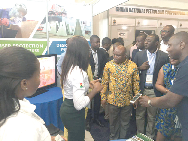 Ms Priscilla Amofah (2nd left) of Seaweld Engineering explaining the company's services to Dr Adam (arrowed left ), Mr Faibille (arrowed right ) and other dignitaries