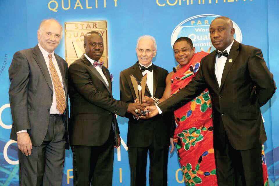 Noble Agyei-Poku CEO (right), Nana Dr Appiagyei Dankawoso I (in cloth) and Lawyer Asante Krobea, Chairman of the bank (2nd left) receiving the award in France from a representative  of BLD