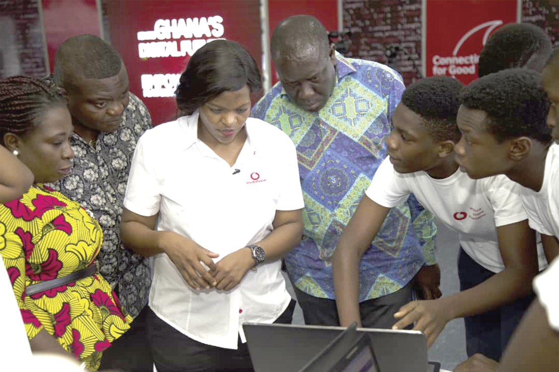 Mr Vincent Sowah Odotei (middle) and Ms Yolanda Cuba (3rd left) inspecting some of the application softwares developed by an initial group of young people.
